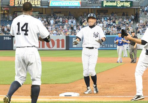 ヤンキース対ブルージェイズ 1回、日米通算4000本安打を達成したイチローは、ベンチを飛び出し祝福に向かうナインに照れ笑いを見せる(撮影は2013年8月21日)