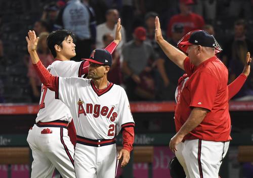 ロッキーズに勝利し、ソーシア監督(右)にタッチで迎えられるエンゼルス大谷(撮影・菅敏)