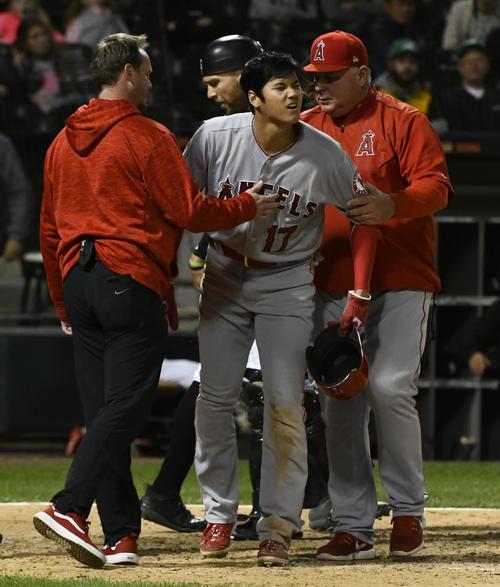 本塁でベースカバーに入った投手と交錯、立ち上がったが痛そうな表情を見せる大谷(AP)