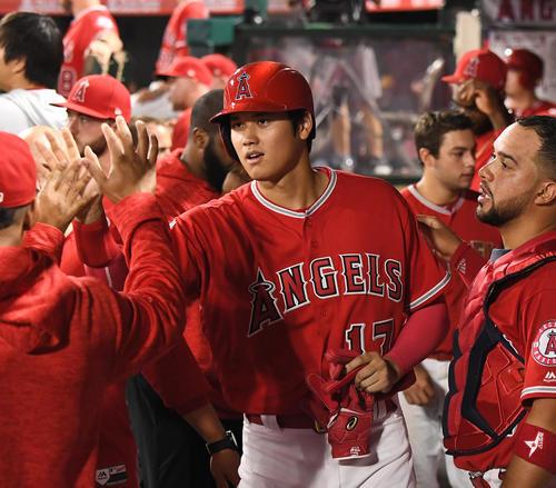 エンゼルス対レンジャーズ 3回裏エンゼルス2死二塁、アップトンの適時三塁打で二塁から生還し、ナインにタッチで迎えられるエンゼルス大谷(撮影・菅敏)