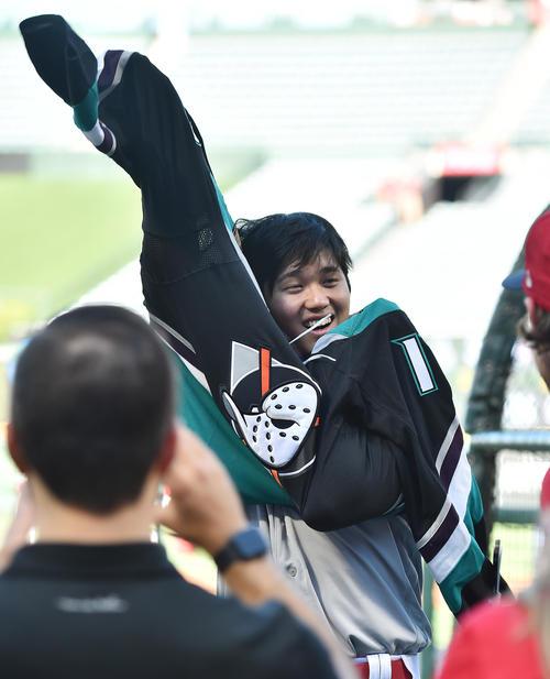NHLアナハイムダックスから贈られたユニホームに笑顔で袖を通すエンゼルス大谷(撮影・菅敏)