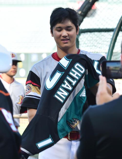 NHLアナハイムダックスから贈られたユニホームに袖を通すエンゼルス大谷(撮影・菅敏)