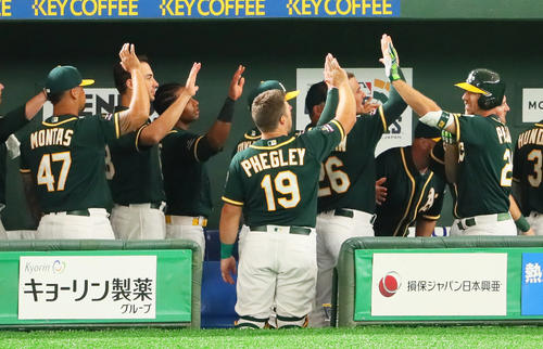 日本ハム対アスレチックス 2回表アスレチックス無死、ピスコティ(右端)は左越え本塁打を放ちナインとタッチを交わす(撮影・足立雅史)