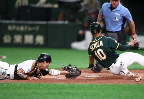日本ハム対アスレチックス 4回表アスレチックス2死一塁、失策の間に本塁に突入するセミエンを本塁で刺す中田。捕手郡(撮影・黒川智章)