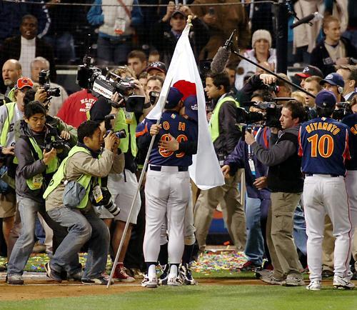 06年3月、初優勝を決めたセレモニーで、日の丸の旗を持って整列するイチローはそのまま王貞治監督と抱擁し、旗にくるまれる