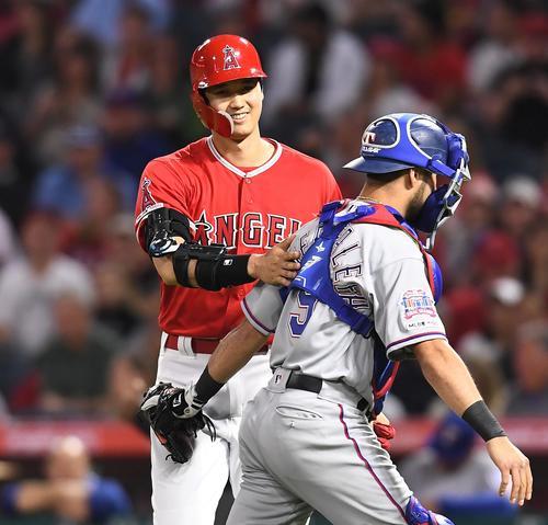 エンゼルス対レンジャーズ 3回裏エンゼルス無死、一塁への打球で一塁に駆け込みセーフとジャッジされるもチャレンジの結果、アウトとなりベンチに戻るエンゼルス大谷。捕手カイナーファレファ(右)と交錯しそうになり、苦笑いを浮かべる(撮影・菅敏)