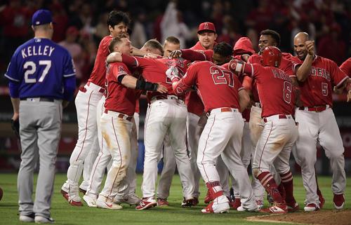 9回、サヨナラ打を放ったウォルシュ(左から4人目)に手荒い祝福をする大谷(左端)らエンゼルスの選手たち。左は投手ケリー(AP)