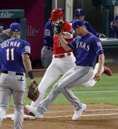 レンジャーズ戦の4回、一塁へのゴロを放ち、一塁へ駆け込むエンゼルス・大谷(中央)。右はベースカバーの投手マイナー。ビデオ判定でセーフとなる(共同)