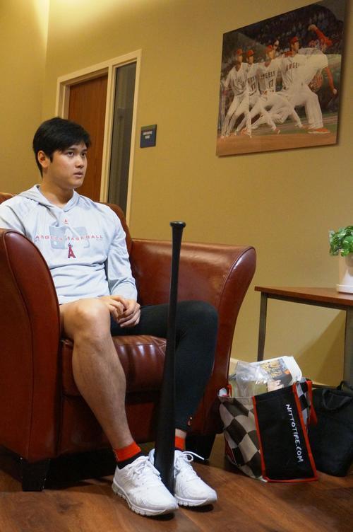 エンゼルスタジアム内に飾られた自信の投球連続写真を背に、インタビューに答える大谷