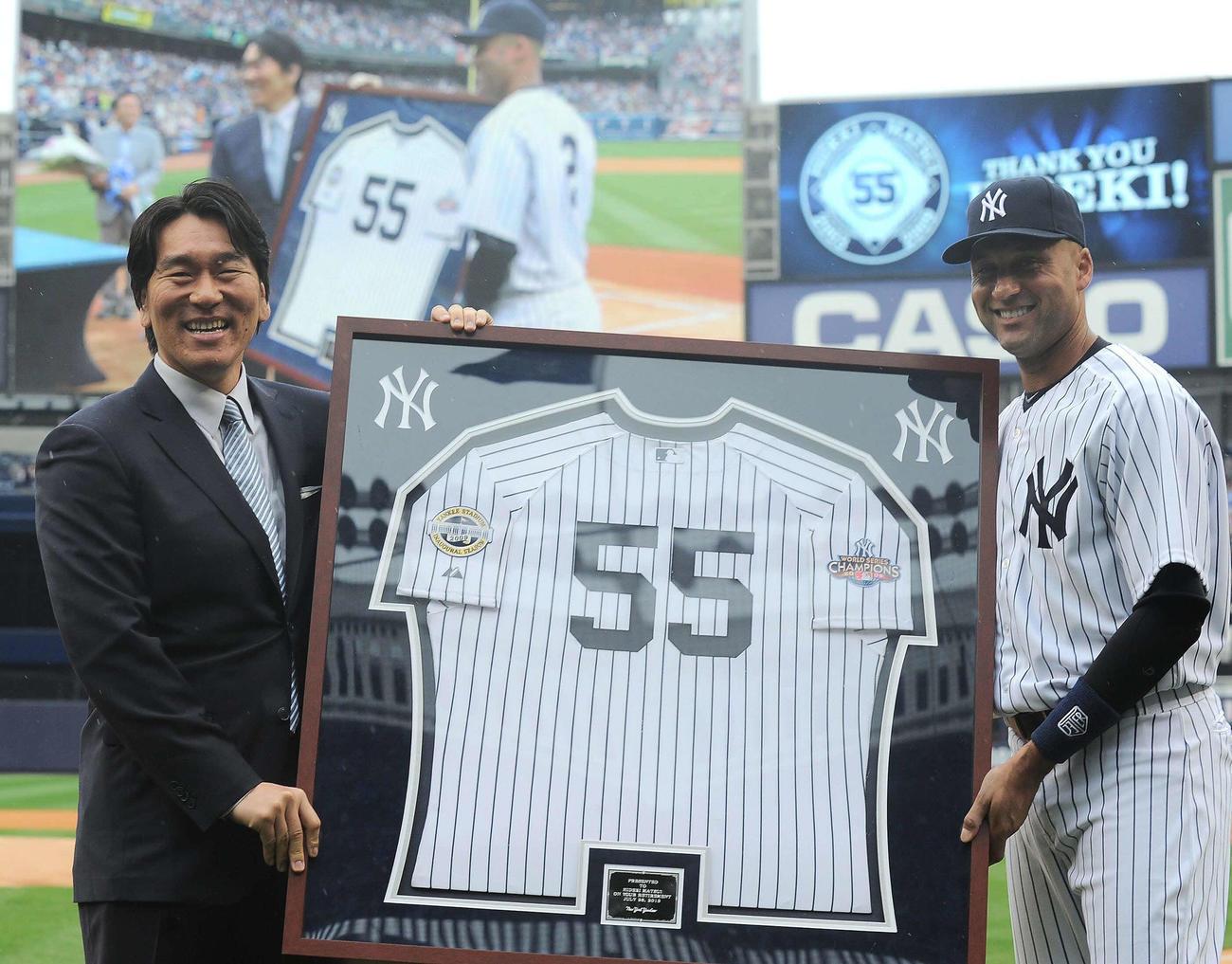 引退式セレモニーで55番のユニホームをジーター(右)から受け取る松井秀喜氏(2013年7月28日撮影)