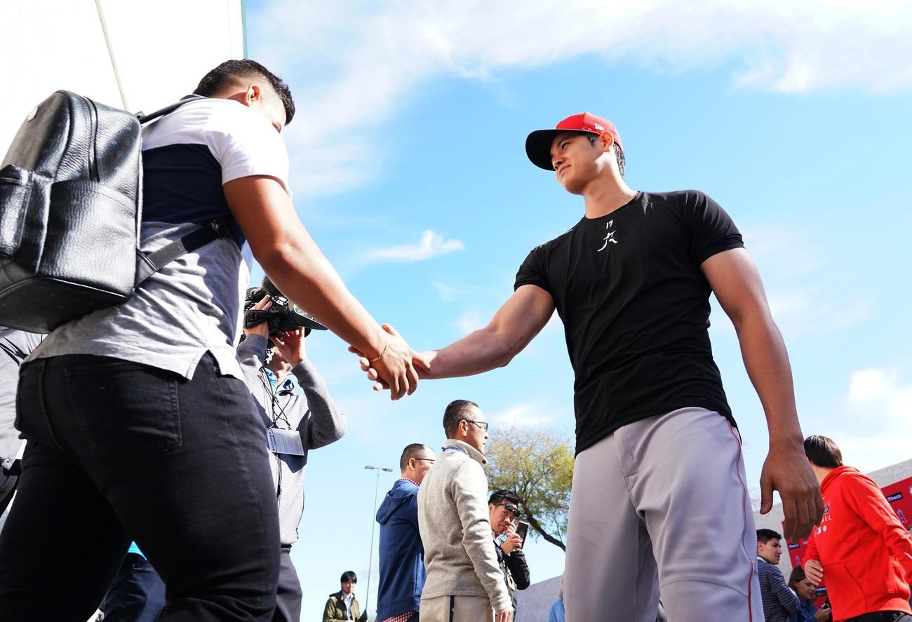 キャンプ初日を終え、ひと足先に引き揚げる同僚を握手で送るエンゼルス大谷(撮影・菅敏)