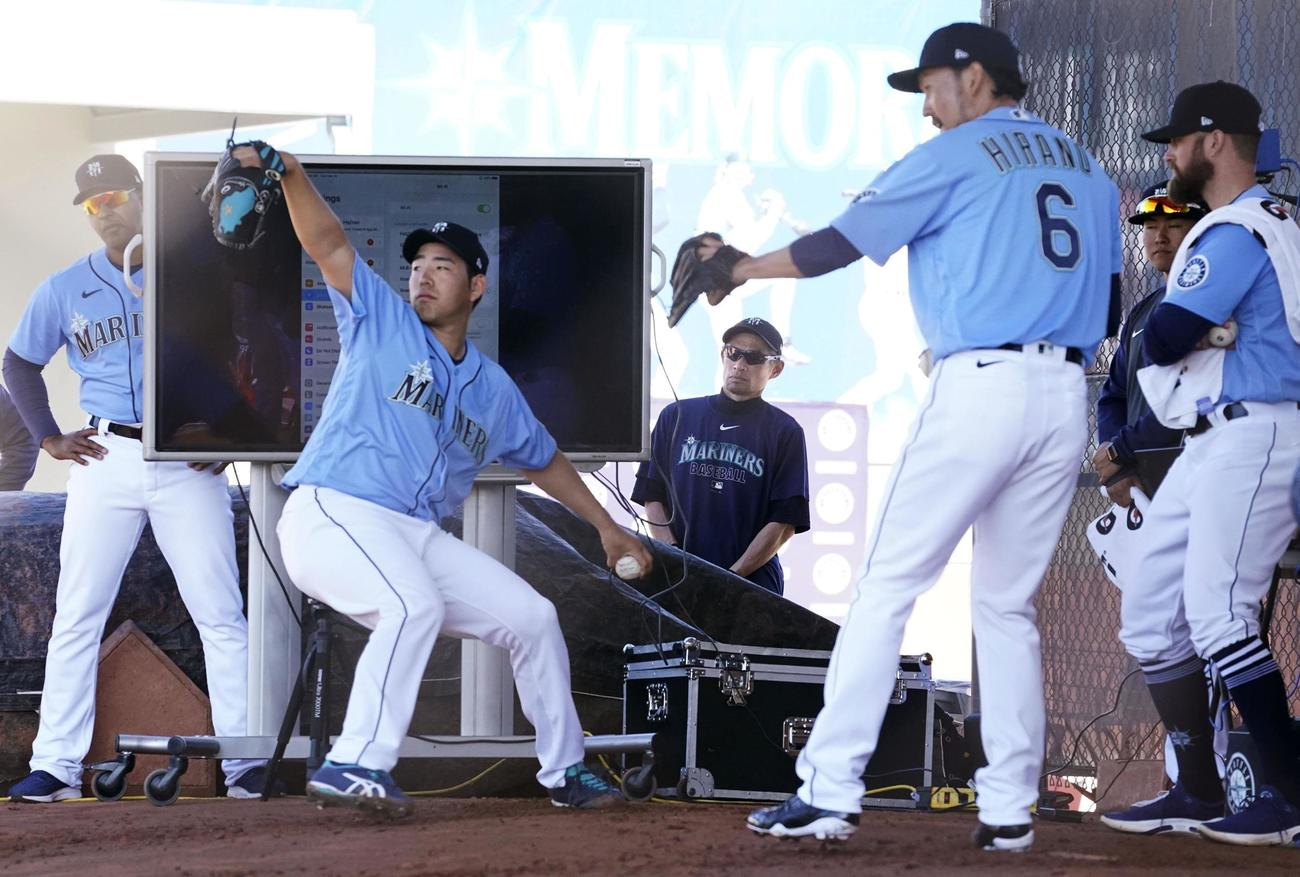 ブルペンで投球練習するマリナーズ・菊池と平野(背番6)を見守るイチローさん(奥中央)(共同)