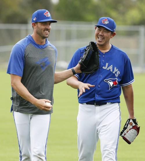 練習を終え、コーチ(左)と笑顔で話すブルージェイズ山口(共同)