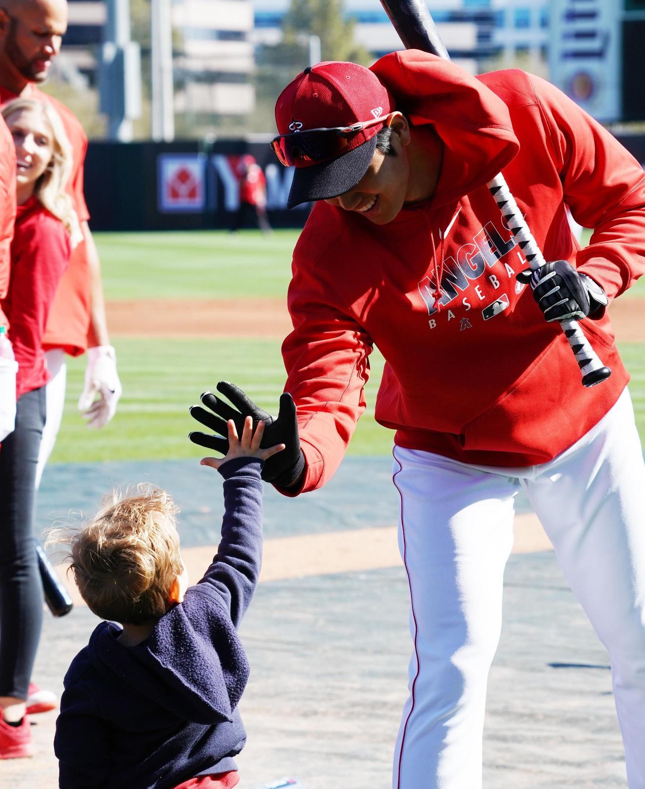 練習中、チーム関係者の子供とタッチをするエンゼルス大谷(撮影・菅敏)