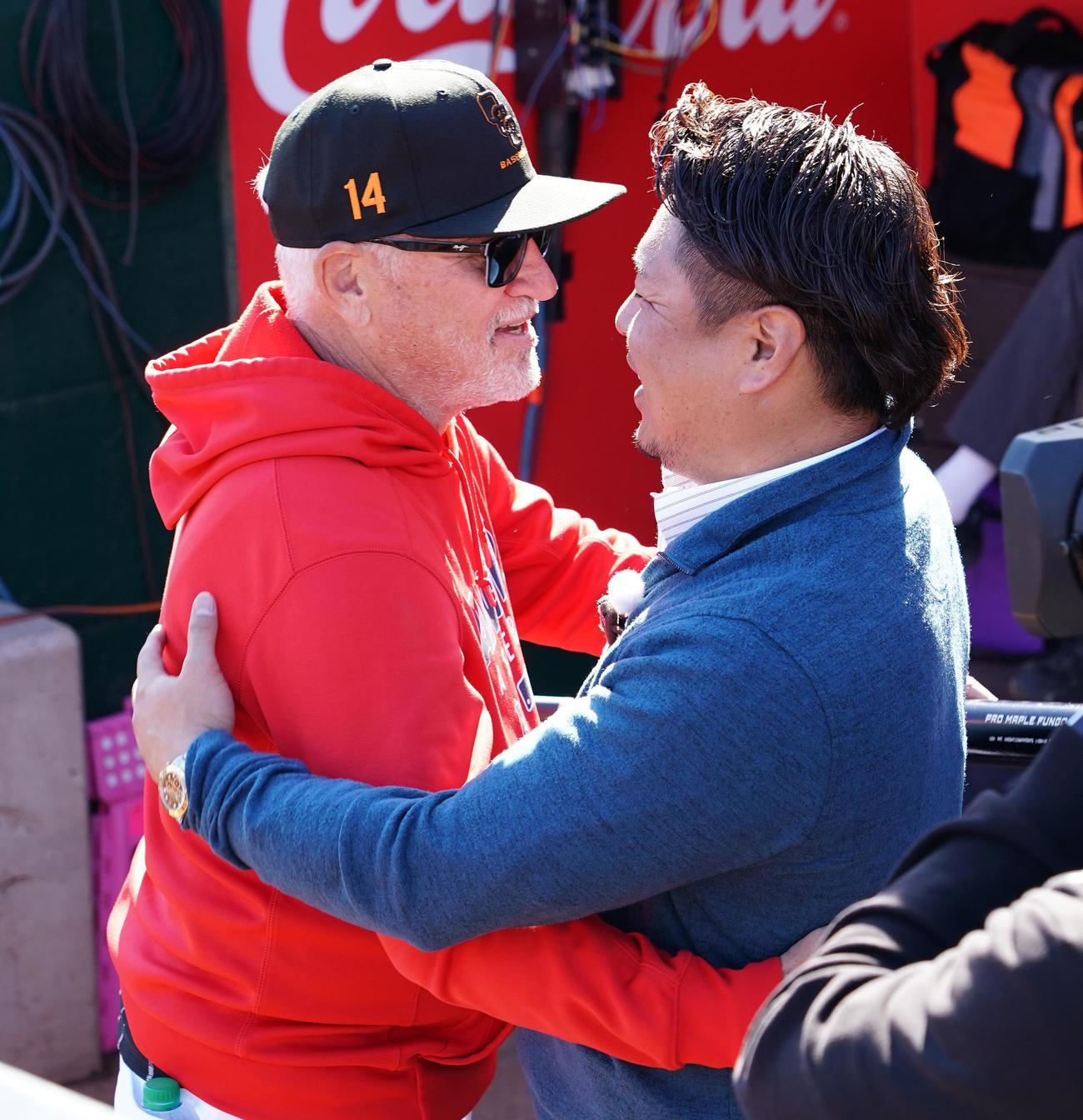 エンゼルスのキャンプ地を訪れ、マドン監督(左)と再会し、笑顔でハグする岩村氏(撮影・菅敏)