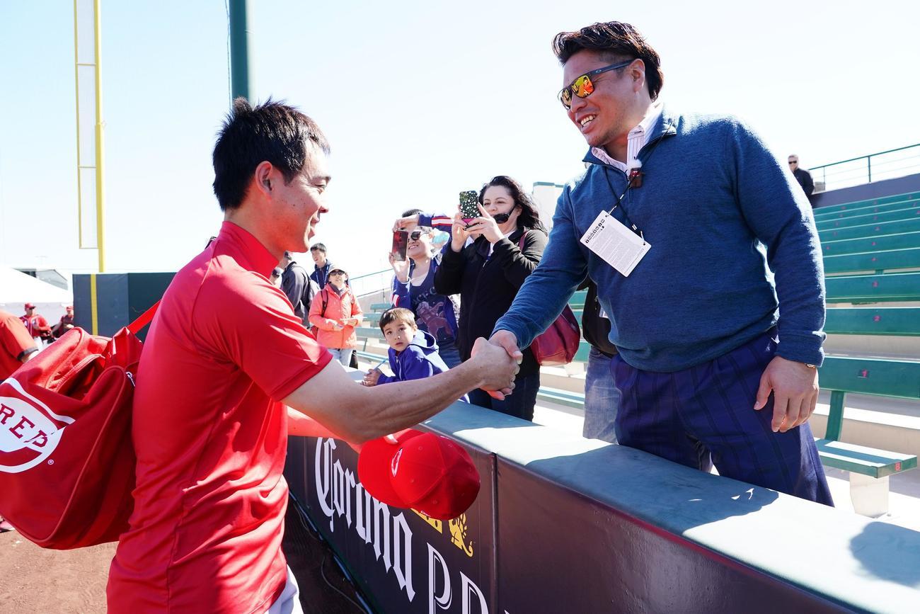 オープン戦エンゼルス対レッズ戦を訪れた岩村氏(右)から激励を受けるレッズ秋山(撮影・菅敏)