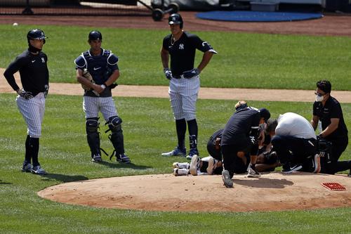 頭部に打球を受けた田中の様子を見るスタッフたち(AP)