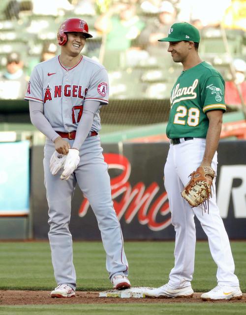 アスレチックス戦の2回、安打を放って一塁手オルソン(右)と談笑するエンゼルス大谷(共同)