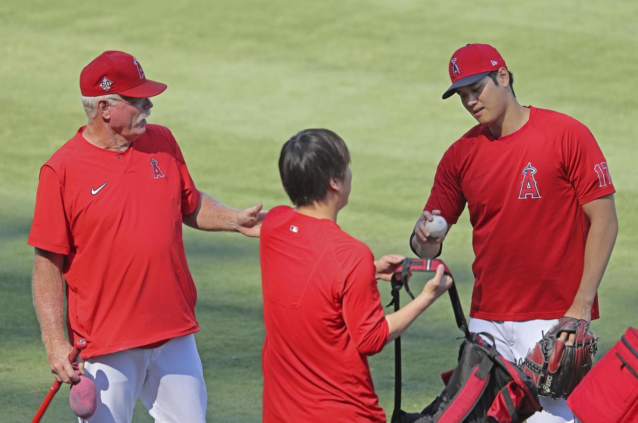 試合前にコーチ(左)と話すエンゼルス大谷(共同)