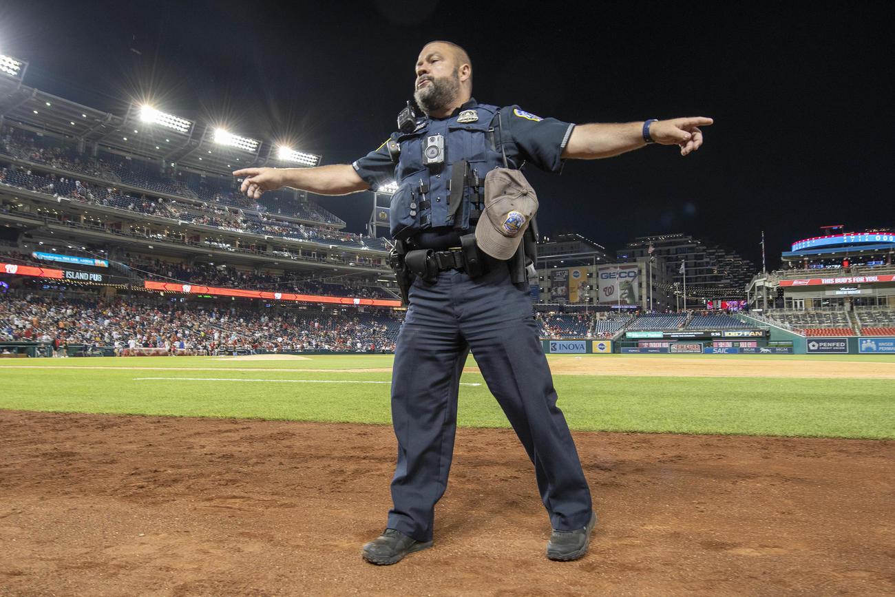 17日、ナショナルズ-パドレス戦の最中に球場近くで銃撃事件が発生したため観客に避難を指示する警察官(USA TODAY)