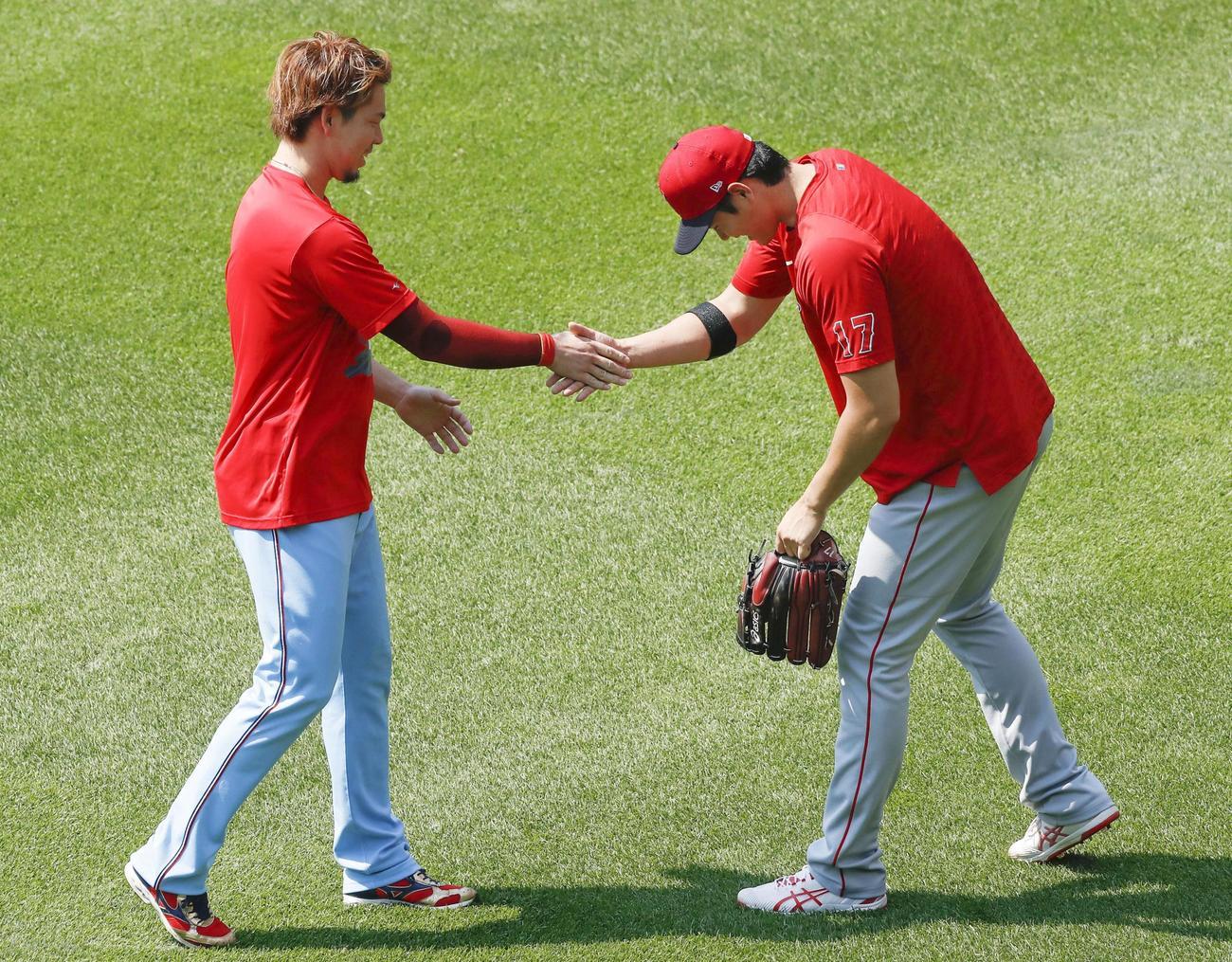 試合前、ツインズ前田(左)と握手するエンゼルス大谷(共同)