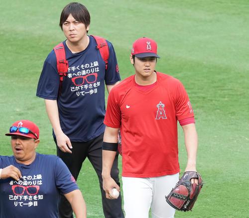 エンゼルス対アストロズ 試合前の練習を終え、日本語でメッセージがプリントされたTシャツを着た水原通訳(中央)と引き揚げるエンゼルス大谷(撮影・菅敏)