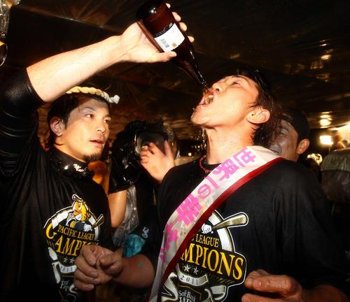 祝勝会で松田宣浩(左)からビールを飲まされる内川聖一