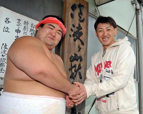 琴奨菊(左)と笑顔で握手を交わす内川(2013年10月31日、福岡県糟屋郡久山町久原、佐渡ケ嶽部屋)