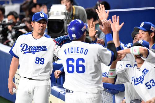 1回裏中日2死二塁、福田の右前適時打で生還したビシエド(右)を迎える松坂(撮影・前岡正明)