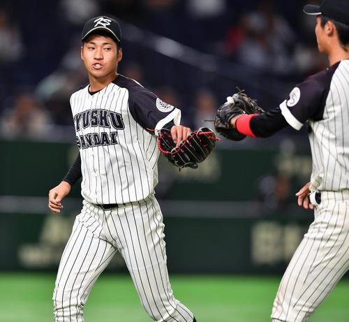 東海大対九産大 5回を抑えた九産大・岩田(左)は森一塁手とグラブタッチする(撮影・柴田隆二)