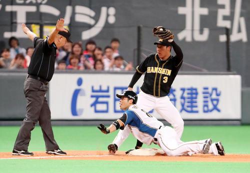 日本ハム対阪神 8回裏日本ハム無死一、二塁、近藤は中越え適時三塁打を放ちヘッドスライディングする、右は大山(撮影・加藤哉)