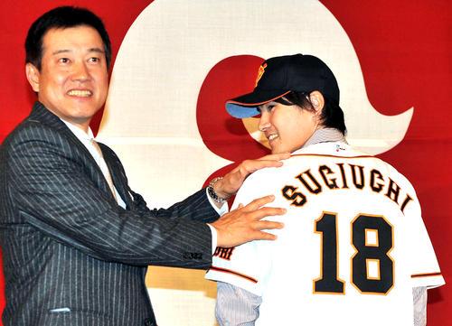 11年12月、巨人入団会見で杉内(右)は、背番号18のユニホームに袖を通し原監督(左)と笑顔を見せる