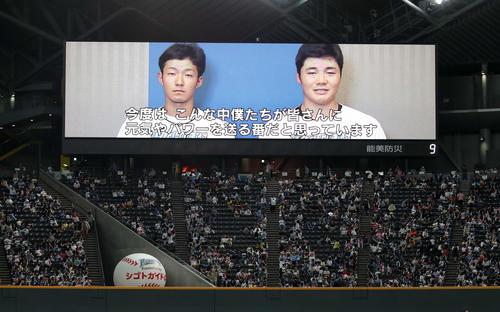 大型ビジョンに流れる、日本ハム石井一(左)と清宮の被災者へのメッセージ(撮影・佐藤翔太)