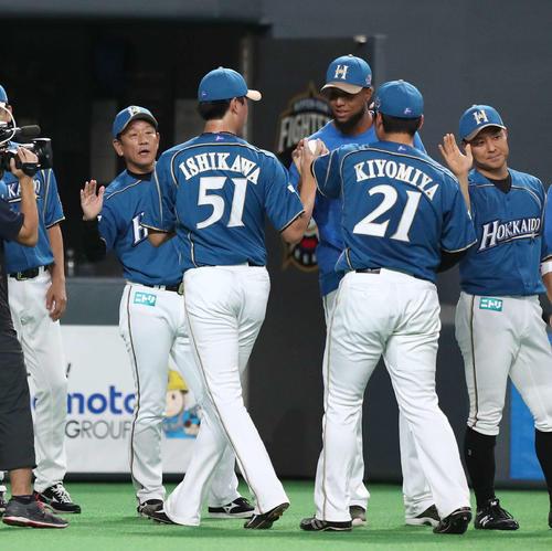 試合後、ナインを出迎える栗山監督(左)(撮影・黒川智章)