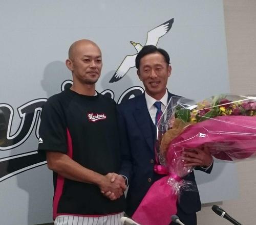 引退会見でサプライズで福浦から花束を渡され、目に涙を浮かべたロッテ岡田(右)