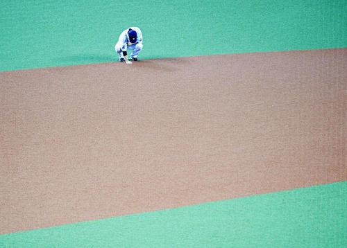 レフトスタンドのファンにあいさつをした後、ショートの守備位置に手を置きグラウンドに別れを告げる西武松井(撮影・横山健太)