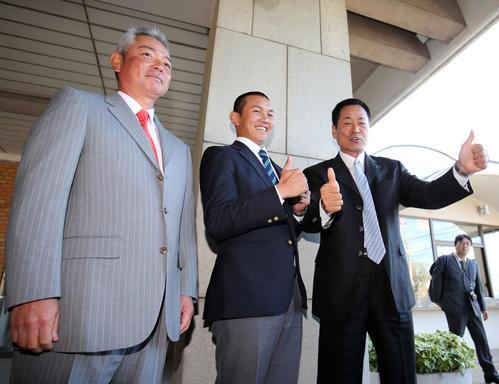 14年10月、DeNA1位指名を受けた亜大・山崎(中央)は中畑監督(右)の勢いに圧倒される。左は亜大・生田監督
