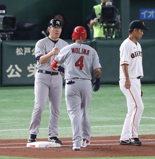 巨人対MLB 1回表MLB1死、中前打を決めたモリーナとグータッチするMLB松井コーチ(撮影・林敏行)