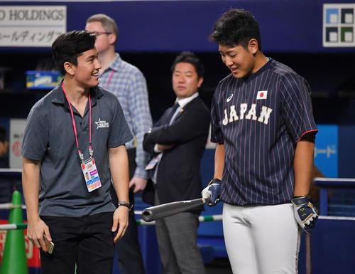 MLB対日本 関係者からヘルナンデスのバットを受け取り笑顔の岡本(右)(撮影・滝沢徹郎)