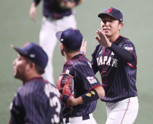MLB対日本 4回裏を終え、菊池(中央)とタッチを交わす笠原(撮影・狩俣裕三)