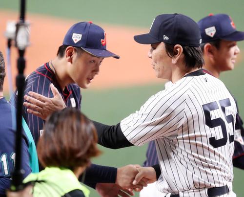 MLB対日本 試合後、岡本(左)と握手を交わす松井コーチ(撮影・狩俣裕三)