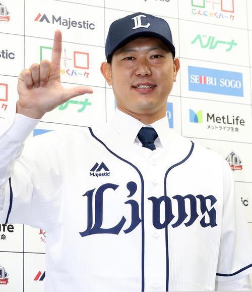 西武入団会見でユニホームを着用し笑顔で「L」ポーズをとる内海(撮影・浅見桂子)