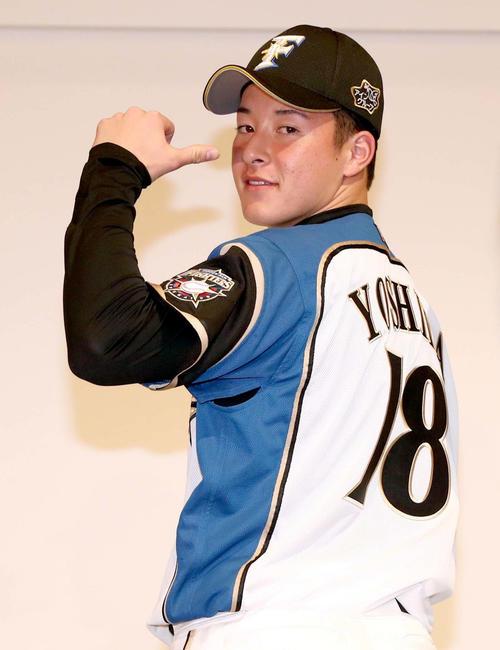新入団選手発表で背番号「18」を披露する吉田輝(撮影・黒川智章)