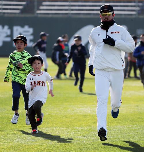 選手たちと並んでウオーミングアップする子どもと併走しておどける巨人陽(右)(撮影・垰建太)