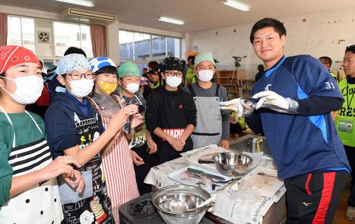 実家が漁業を営む西武佐藤龍世は魚の下ごしらえもお手のもの?地元の小学生とともに食材の「トビウオ」を器用にさばく(撮影・たえ見朱実)