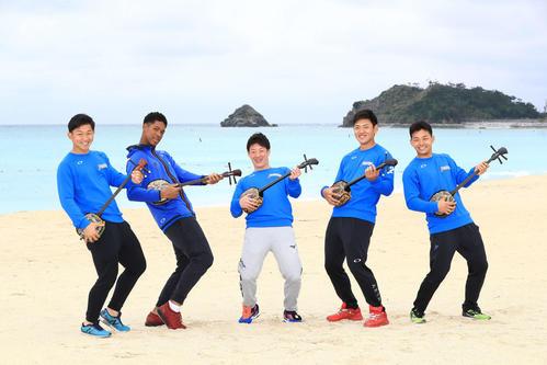 キャンプ休日に三線を体験しビーチで記念撮影する吉田輝(中央)ら日本ハムの新人選手。左から柿木、万波、1人おいて野村、田宮(撮影・江口和貴)