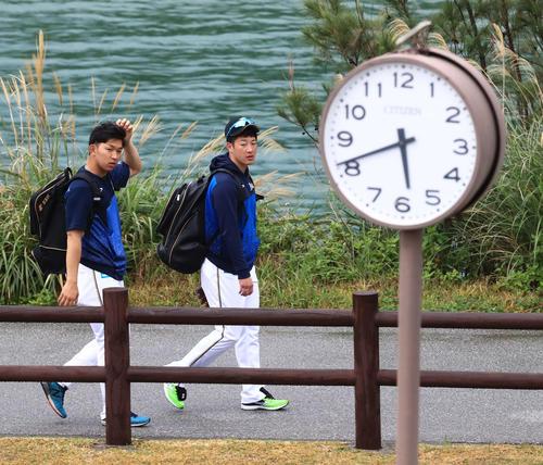 早朝練習か!?時計が5時40分過ぎを表示する中、球場入りする日本ハム吉田輝(右)と柿木。実は時計調整中で、通常の午前8時20分の入りでした(撮影・江口和貴)
