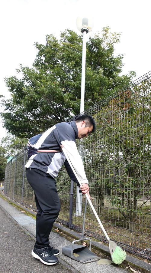 柳田悠岐のロングティーのボールが当たり破壊された外灯の破片を片づける球場関係者(撮影・菊川光一)