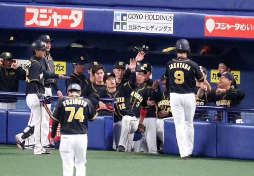 2回表阪神無死一、三塁、高山は右前適時打を放ち攻守交代でベンチへ戻るとナインから笑顔の出迎えを受ける(撮影・加藤哉)