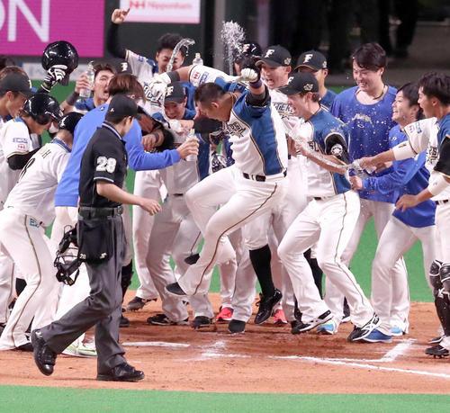10回裏日本ハム1死満塁、サヨナラ満塁本塁打を放った中田(手前中央)はナインの待つ本塁にジャンプして生還する(撮影・黒川智章)